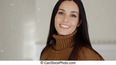 Attractive woman with a warm friendly smile posing indoors...