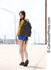 Attractive woman with bag looking back