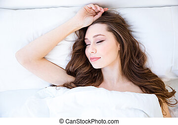 Attractive woman with beautiful long hair sleeping in bed