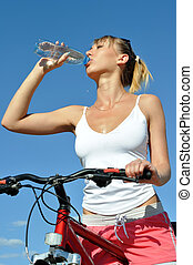 Attractive woman with bike,drinking cold water