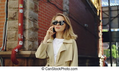 Attractive woman with blond hair is talking on mobile phone walking along street in modern city. Young lady is wearing trendy black sunglasses and summer coat.