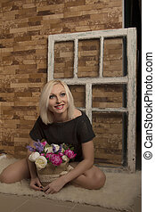Attractive woman with flowers in studio