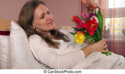 attractive woman with flowers on bed. Female smiling and looking at camera