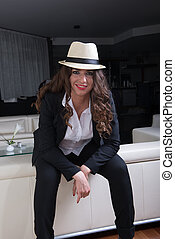 attractive woman with hat in business outfit