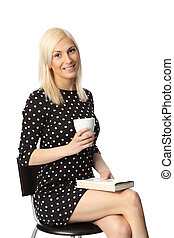 Attractive woman with mug and book