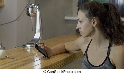 Attractive woman with phone sits at bar desk in apartment.