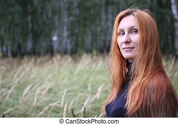 Attractive woman with red hair in the autumn forest