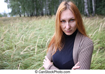 Attractive woman with red hair in the autumn park