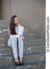 Attractive woman with red lips sitting on stairs