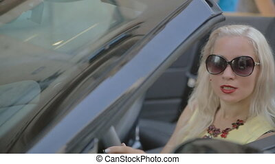 Attractive woman with red lipstick starts the car