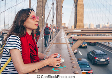 Attractive woman with red scarf on Brooklyn Bridge