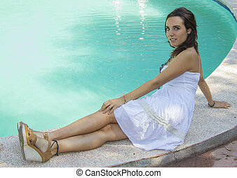 attractive woman with summery white dress sitting on the edge of a pool