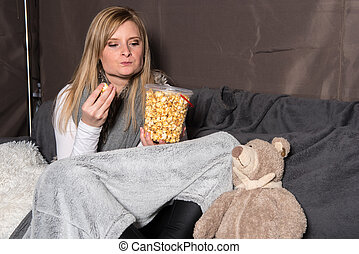 Attractive woman with teddy is looking forward to her popcorn