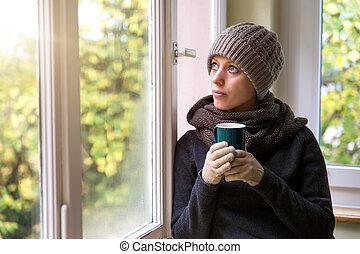 woman with warm knitted clothes is drinking something hot