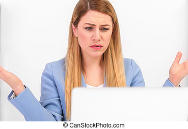 Attractive woman working at a laptop in the misunderstanding of a helpless gesture.