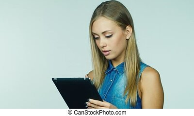 Attractive woman working with a tablet on a white background