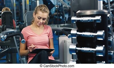 Attractive woman working with the tablet in a sports club