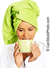 Attractive woman wrapped in towel with turban on head, holding a cup. isolated on white.