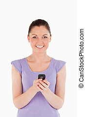 Attractive woman writing a text on her phone while standing