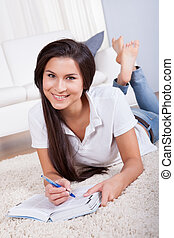Attractive woman writing in a diary