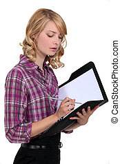 Attractive woman writing in a folder