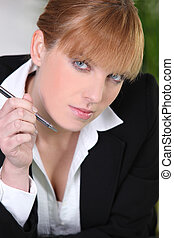 Attractive woman writing in an office