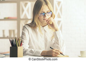 Attractive woman writing in notepad