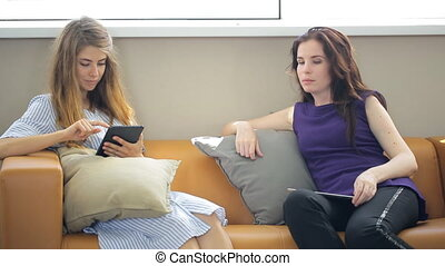 Attractive women, a blonde and a brunette, sitting in office on sofa with a tablet and communicate.