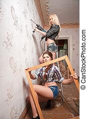 Attractive women do repair in apartment