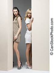 Attractive women hiding theirselves behind the wall -...
