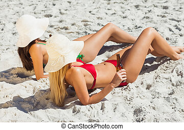 Attractive women in bikinis lying on the sand drinking beer