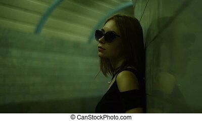 attractive women in sunglasses posing in dark alley -...