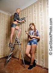 Attractive women make repair in apartment