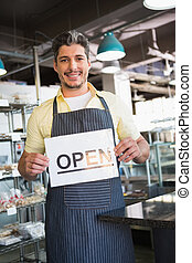 Attractive worker holding open sign