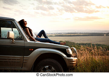 woman is laying on the car's hood - Attractive yong woman is...