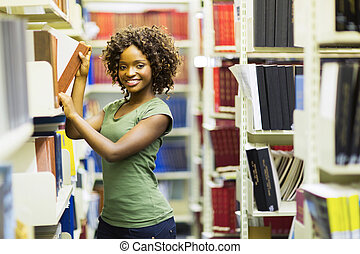 african american college student searching for books in library