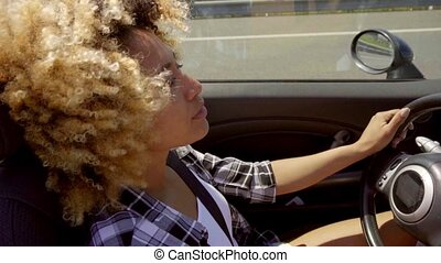 Attractive young African American woman driving a cabriolet ...
