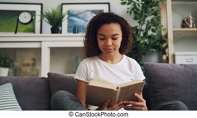 Attractive young African American woman is reading book...