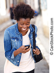 Attractive young african american woman laughing with mobile phone