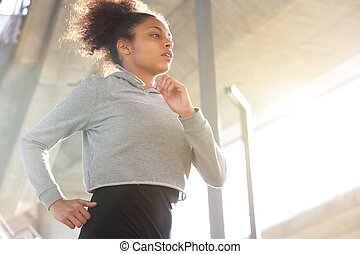 Attractive young african american woman running outdoors -...