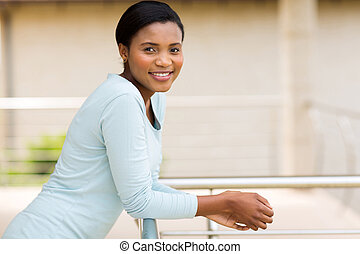 young african american woman relaxing on balcony