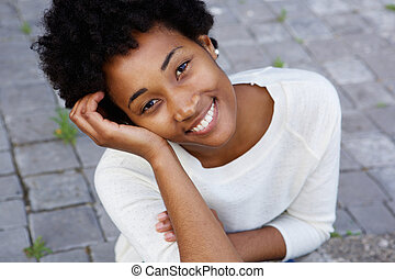 Attractive young african american woman sitting outdoors