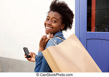 Attractive young african american woman smiling with phone and shopping bag