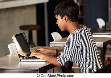 Attractive young african american woman using laptop