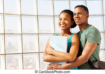 young african college couple embracing