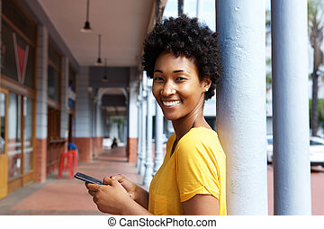 Attractive young african woman holding a mobile phone