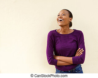 Attractive young african woman laughing against a wall