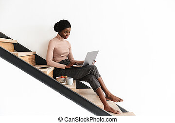 Attractive young african woman sitting on a staircase at home