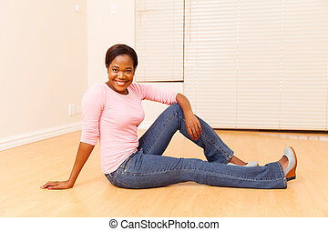 young african woman sitting on wooden floor