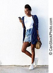 Attractive young african woman using smart phone